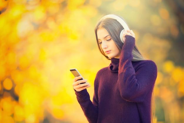 Portrait d'une jeune fille heureuse avec des écouteurs et de la musique d'écoute de smartphone dans le parc d'automne.