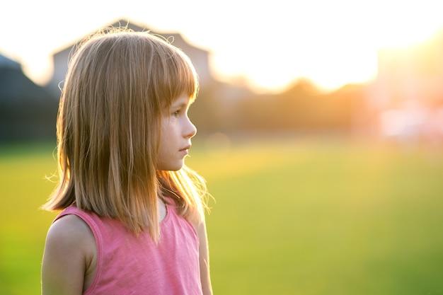 Portrait de jeune fille heureuse d'enfant se détendre à l'extérieur sur une chaude soirée d'été.