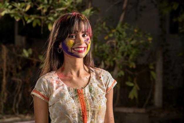 Portrait d'une jeune fille heureuse sur le festival des couleurs holi. fille posant et célébrant le festival des couleurs.