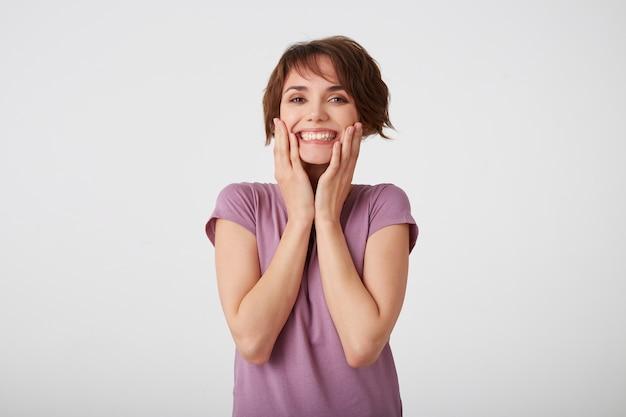 Portrait de jeune fille heureuse mignonne en t-shirt blanc, touche les joues, debout sur un mur blanc et souriant largement. profiter de la journée. concept d'émotion positive.