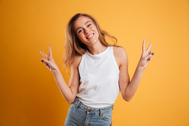 Portrait d'une jeune fille heureuse montrant le geste de paix