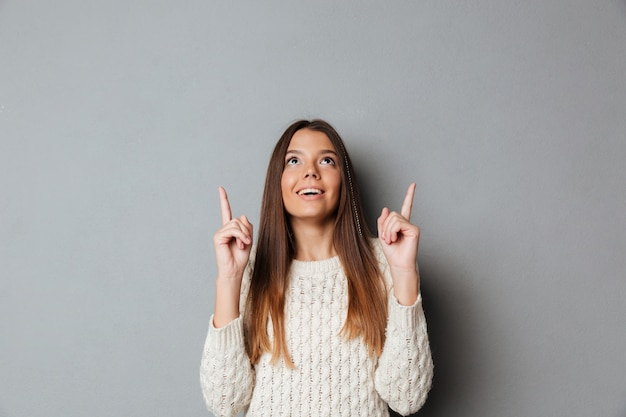 Portrait d'une jeune fille heureuse souriante pointant deux doigts vers le haut