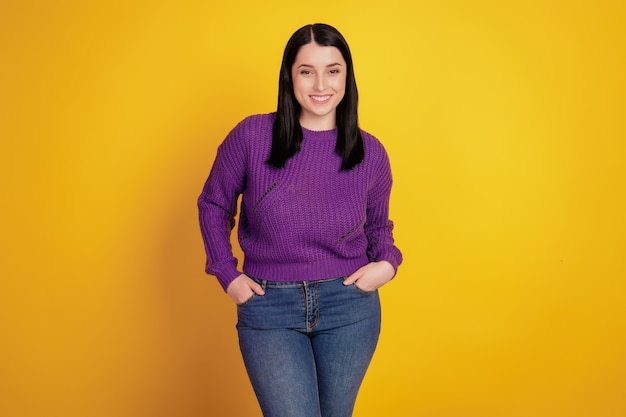Portrait de jeune fille heureuse sourire positif heureux mains dans la poche confiant isolé sur fond de couleur jaune