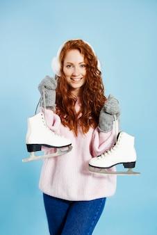 Portrait de jeune fille heureuse tenant des patins à glace