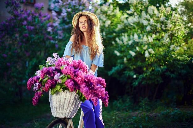 Portrait d'une jeune fille heureuse avec vélo vintage et fleurs sur fond de ville au soleil en plein air.