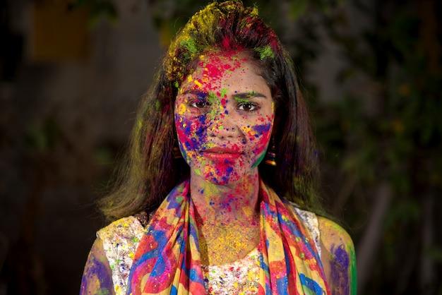 Portrait d'une jeune fille heureuse avec un visage coloré à l'occasion du festival des couleurs holi.