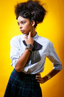 Portrait de jeune fille intelligente sur un mur jaune