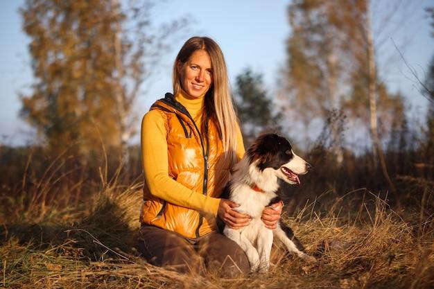 Portrait d'une jeune fille en jaune et border collie sur un fond de nature.