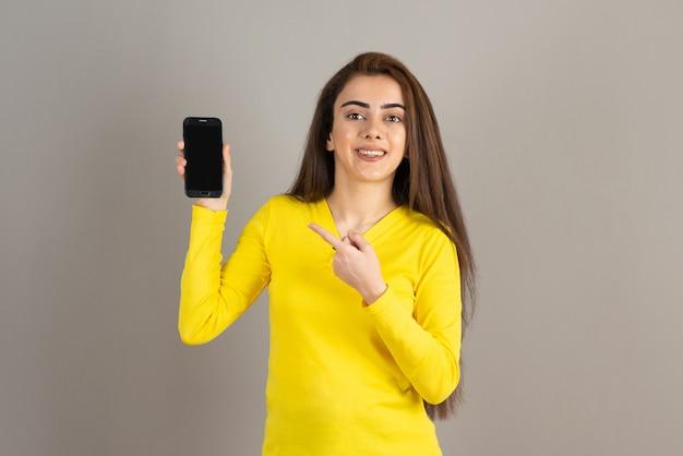 Portrait de jeune fille en jaune tenant un téléphone portable sur un mur gris.