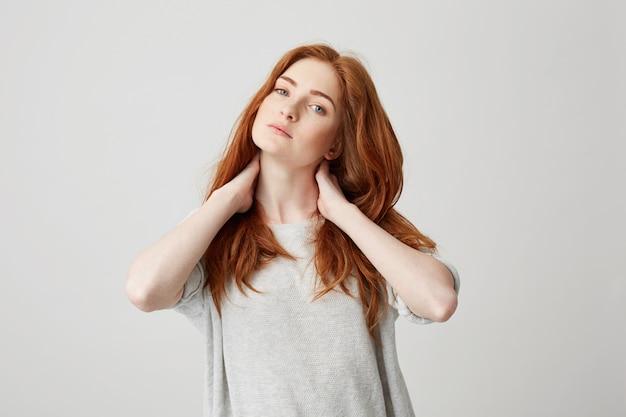 Portrait de jeune fille jolie rousse touchant le cou.