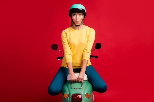 Portrait de jeune fille joyeuse étonné assis sur le visage choqué de cyclomoteur sur le mur rouge