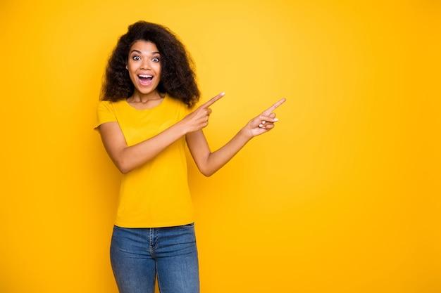 Portrait de jeune fille joyeuse excitée montrant une nouvelle nouveauté