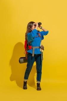 Portrait d'une jeune fille joyeuse touriste avec sac et jumelles isolé sur mur jaune studio