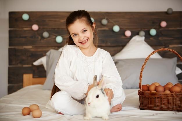 Portrait de jeune fille avec lapin et panier d'oeufs de pâques