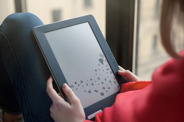 Portrait d'une jeune fille lisant un livre électronique.