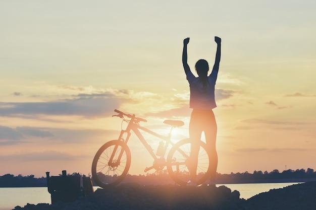 Portrait de jeune fille une main de cycliste lève le soleil car elle gagne.
