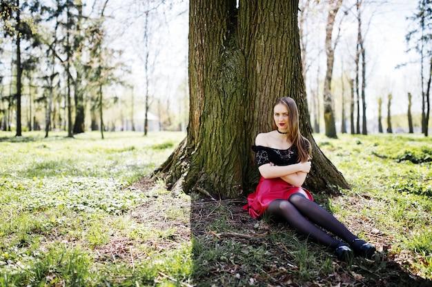 Portrait de jeune fille avec un maquillage lumineux avec des lèvres rouges, un collier noir sur son cou et une jupe en cuir rouge assis près d'un arbre dans un parc.