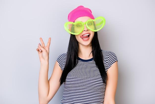 Portrait de jeune fille mignonne au chapeau rose et de grandes lunettes vertes drôles montrant la langue et le signe v