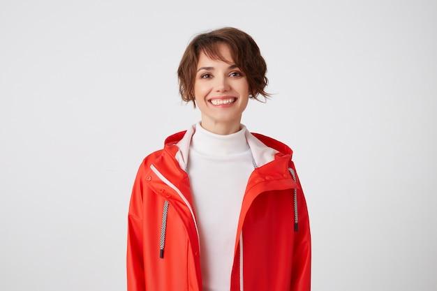 Portrait de jeune fille mignonne aux cheveux courts largement souriante vêtue de golf blanc et manteau de pluie rouge, regardant avec une expression heureuse, debout.