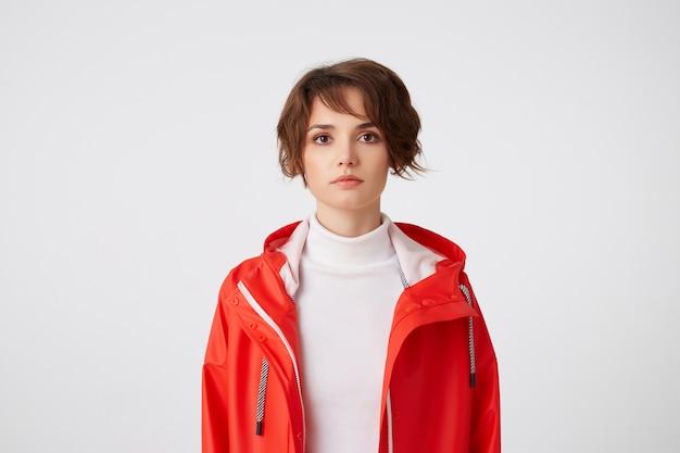 Portrait de jeune fille mignonne aux cheveux courts vêtue de golf blanc et manteau de pluie rouge, regardant avec une expression calme, debout.