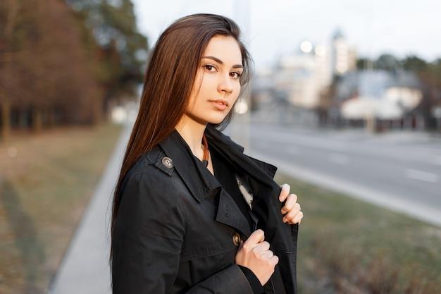 Portrait d'une jeune fille à la mode dans un manteau noir