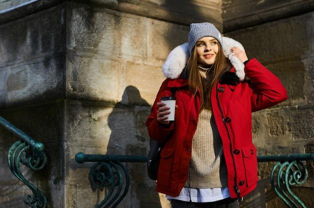 Portrait d'une jeune fille à la mode qui marche dans la rue en hiver