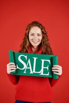 Portrait de jeune fille montrant la bannière de la vente d'hiver