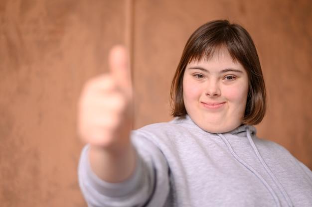 Portrait de jeune fille montrant les pouces vers le haut