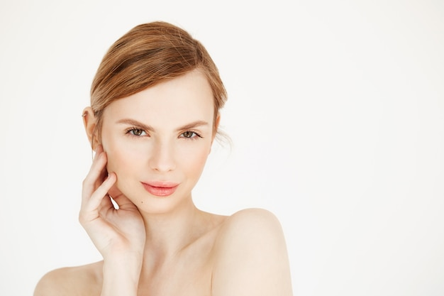 Portrait de jeune fille nue belle souriante visage touchant. traitement facial. cosmétologie de beauté et spa.