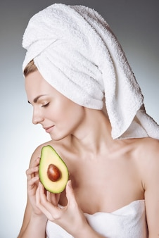 Portrait d'une jeune fille à la peau saine et soyeuse, avec une serviette blanche sur la tête tenant une tranche d'avocat avec une pierre