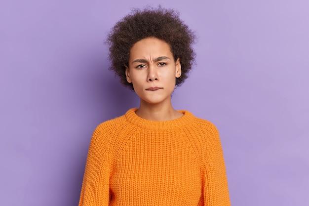 Portrait de jeune fille à la peau sombre insatisfaite avec des cheveux bouclés mord les lèvres fronce les sourcils visage semble mécontent habillé en pull orange tricoté.