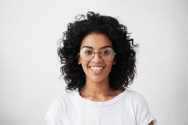 Portrait de jeune fille à la peau sombre insouciante positive habillée avec désinvolture souriant largement