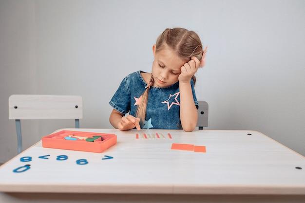Portrait d'une jeune fille pensive fatiguée assis à une table blanche et résolvant des problèmes intellectuels placés sur la table. enfant épuisé. concept de l'enfance. photo avec du bruit