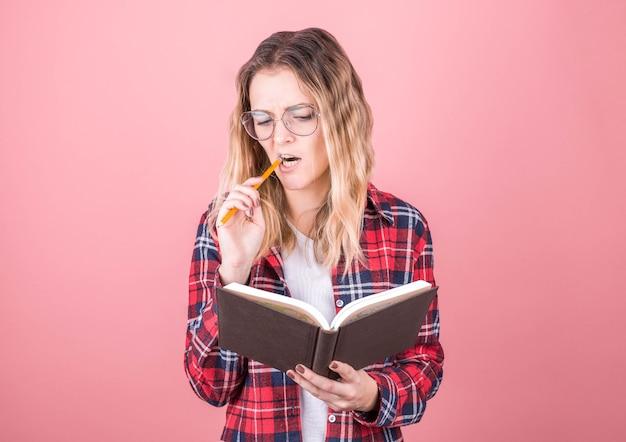 Portrait de jeune fille pensive réfléchie ayant un cahier et un crayon dans la bouche. isolé sur fond rose avec espace copie.