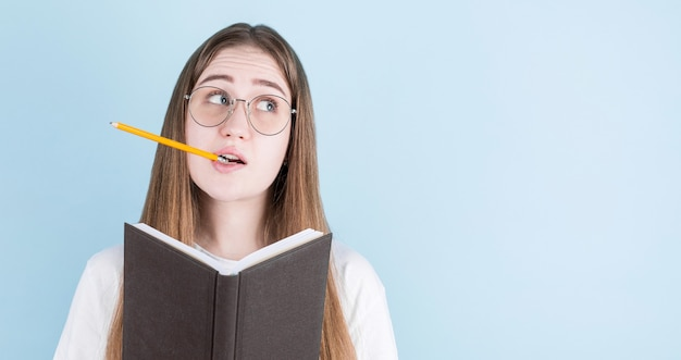 Portrait de jeune fille pensive réfléchie ayant un cahier et un crayon dans la bouche, regardant sur le bleu