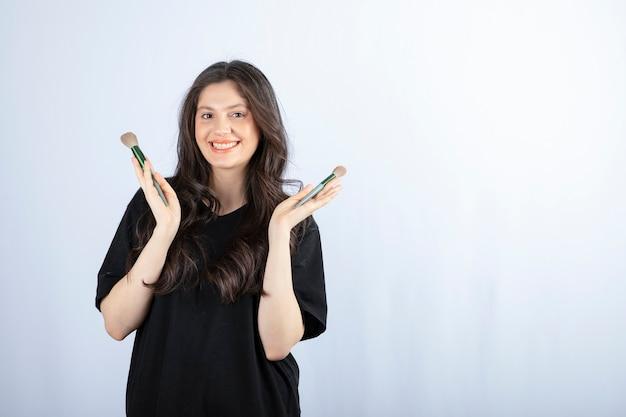 Portrait de jeune fille avec des pinceaux cosmétiques regardant la caméra sur blanc.
