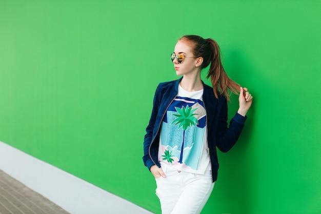 Un portrait d'une jeune fille en plein air près du mur vert avec une ligne blanche vers le bas. la fille porte des lunettes de soleil, tient la queue des cheveux dans la main et regarde au loin.