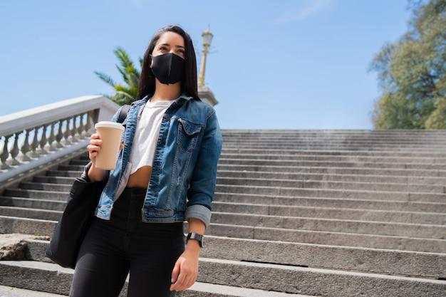 Portrait d'une jeune fille portant un masque tenant une tasse
