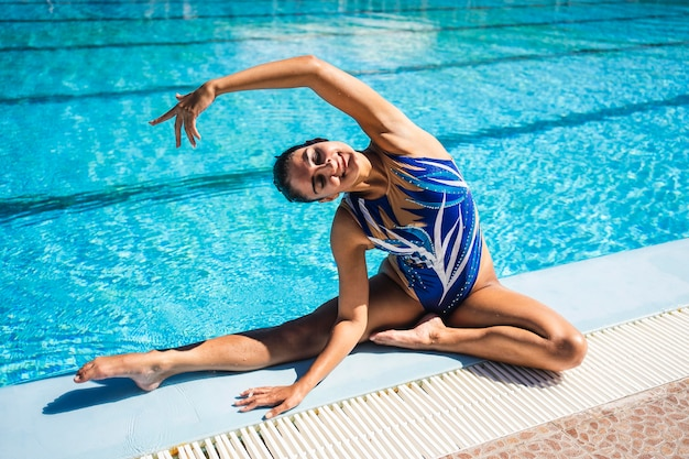 Portrait de jeune fille posant au bord de la piscine