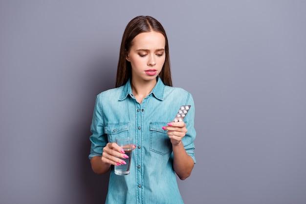 Portrait de jeune fille posant contre un mur gris