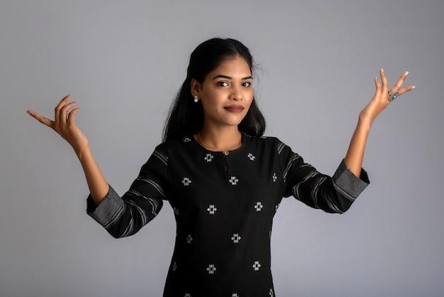 Portrait d'une jeune fille posant sur fond gris