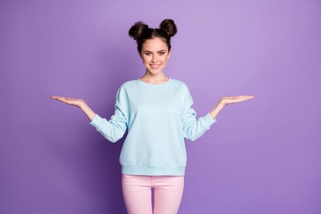 Portrait d'une jeune fille positive et confiante, une promotrice se tenant la main présente des annonces d'objets promotionnels portant un beau pantalon de vêtements isolé sur fond violet