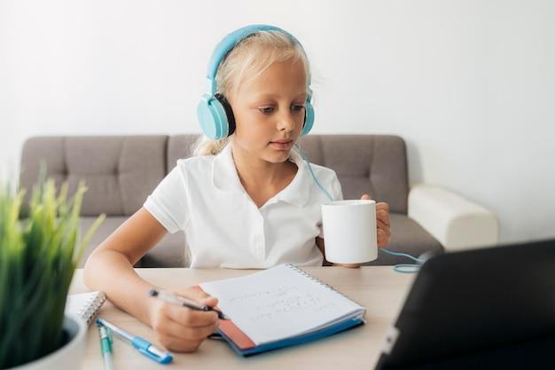 Portrait d'une jeune fille prêtant attention à la classe en ligne