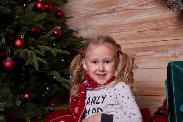 Portrait de jeune fille en pyjama assise sur le lit sous l'arbre de noël avec des cadeaux dans des coffrets cadeaux.