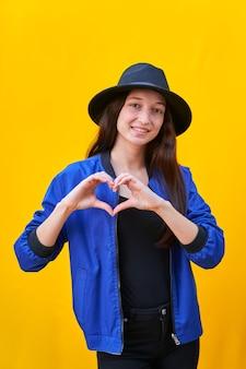 Portrait d'une jeune fille de race blanche au chapeau noir et veste bleue, faisant un coeur avec ses mains