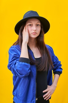 Portrait d'une jeune fille de race blanche au chapeau noir et veste bleue, main sur le visage