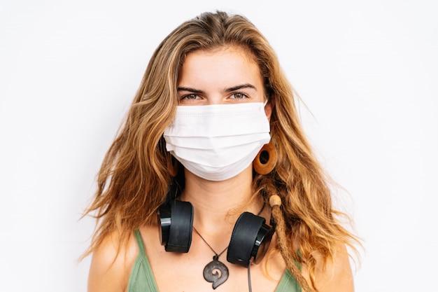 Portrait d'une jeune fille de race blanche avec un casque et un masque médical.