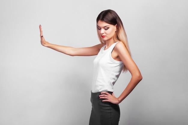 Portrait de jeune fille réfléchie assez confiant, debout sur un mur gris avec copie espace