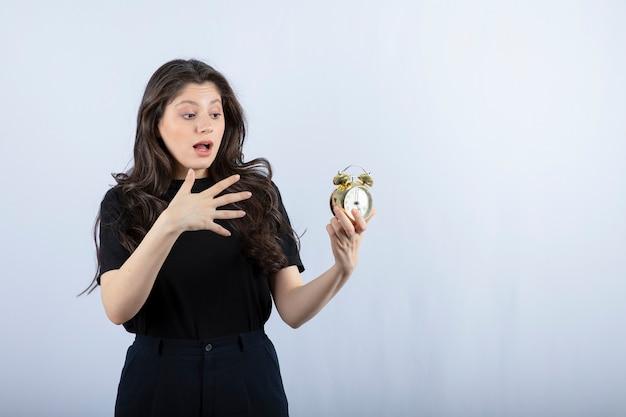 Portrait de jeune fille avec réveil choqué sur le mur blanc.