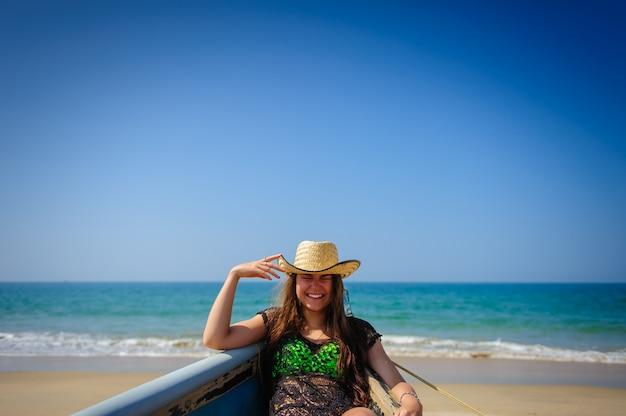 Portrait de jeune fille riante avec de belles dents blanches sur fond de plage de sable, mer turquoise et ciel bleu lumineux